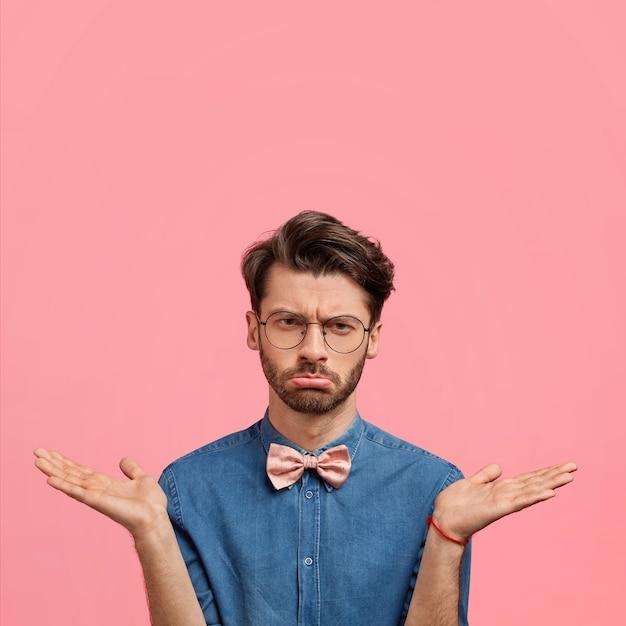 Giovane con occhiali rotondi e papillon rosa Foto Gratuite