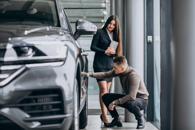 Young man with saleswoman at a car showroom Free Photo