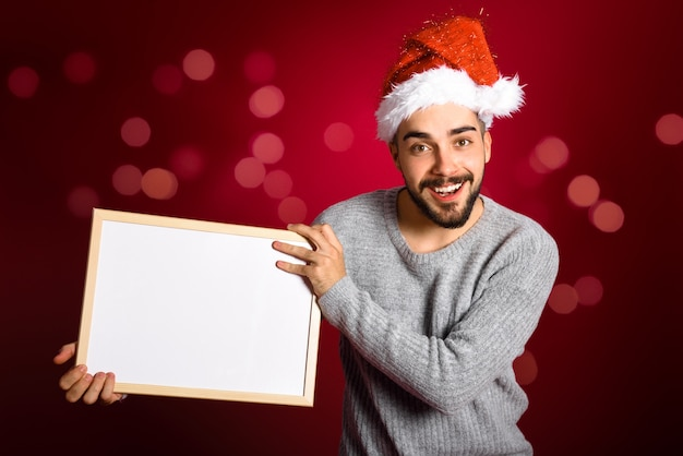 Young man with santa hat holding blank board on red background Free Photo