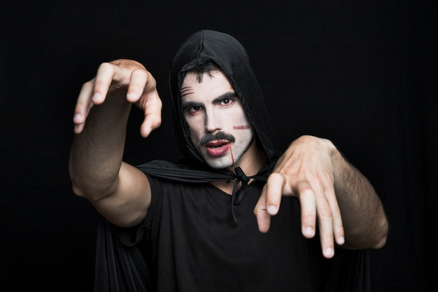Young man with scars on pale face in halloween costume posing in studio Free Photo