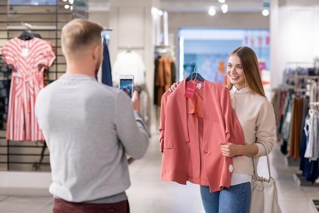 ショッピングモールで一緒に買い物をしながら50パーセント割引でピンクのジャケットを保持している彼のガールフレンドの写真を撮るスマートフォンを持つ若者 Premium写真