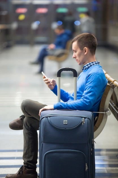 Young man with smartphone waiting for transport Free Photo