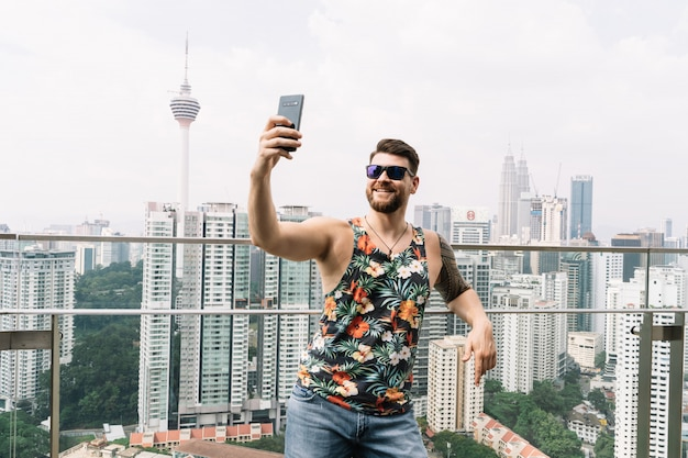 Молодой человек в темных очках и безрукавке с цветочным принтом делает селфи с городом Premium Фотографии