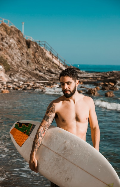 Young man with surf board on beach near water Free Photo
