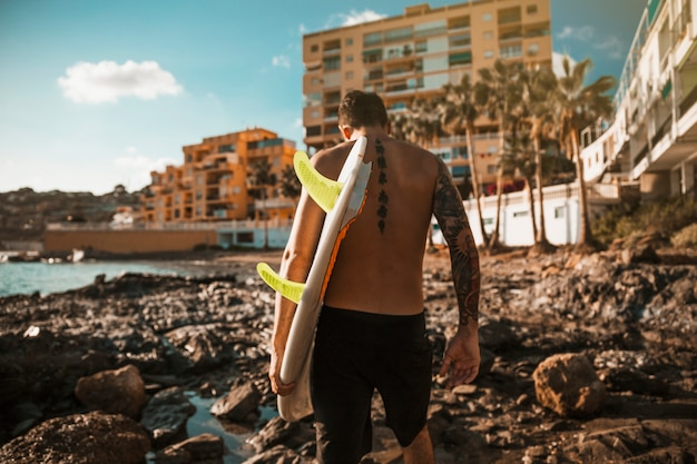 Young man with surf board going on rock shore near water and buildings Free Photo