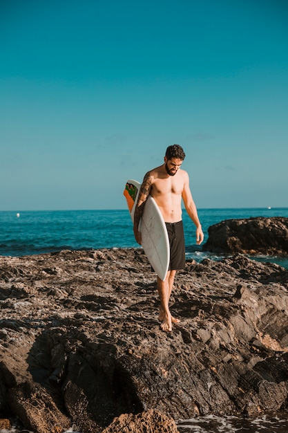 Young man with surf board goingon stone shore near water Free Photo