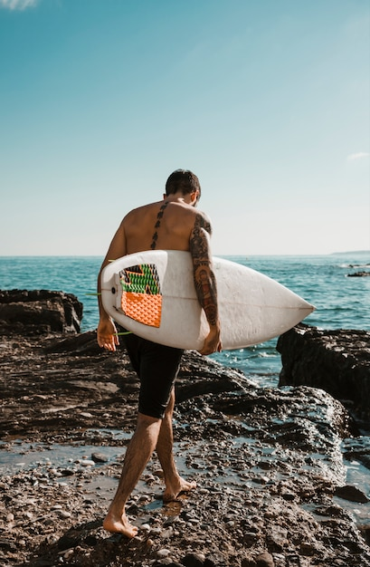 Young man with surf board going to water Free Photo