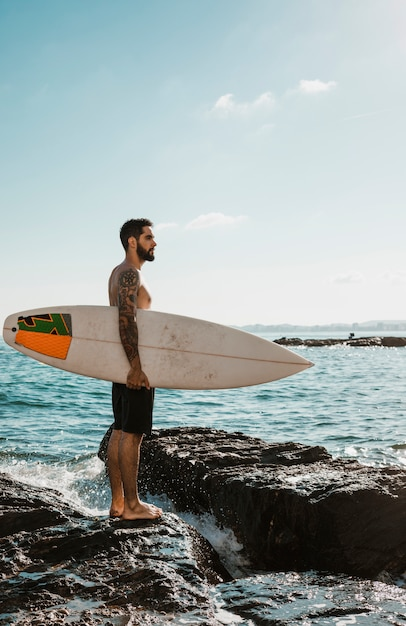 Young man with surf board on rock near water Free Photo