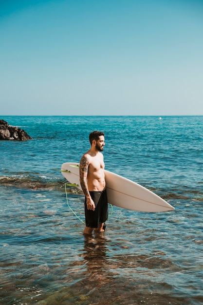 Young man with surf board in water Free Photo