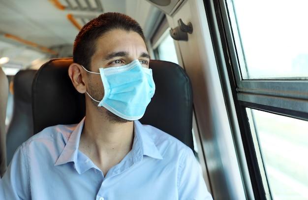 Молодой человек с хирургической маской, глядя через окно поезда Premium Фотографии