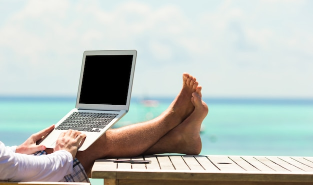Young man with tablet computer during tropical beach vacation Premium Photo