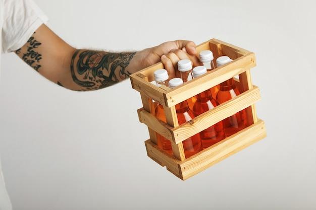 Giovane uomo con tatuaggi tiene una scatola di aranciata in bottiglie senza etichetta, vicino isolato su bianco Foto Gratuite