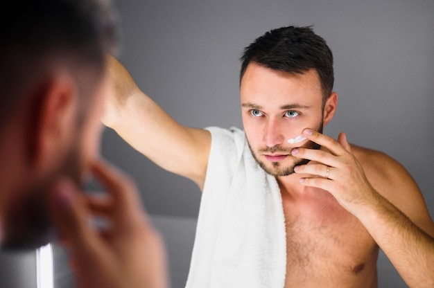 Young man with towel on his shoulder looking in the mirror Free Photo