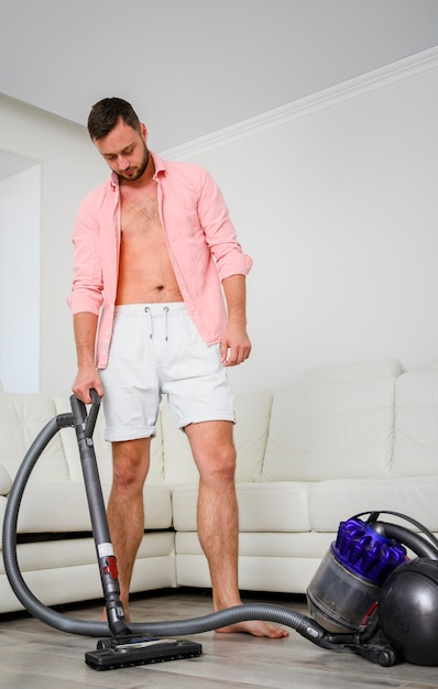 Young man with vacuum cleaner in room Free Photo