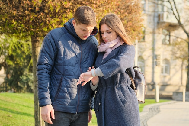 Young man and woman in city, looking at wristwatch Premium Photo