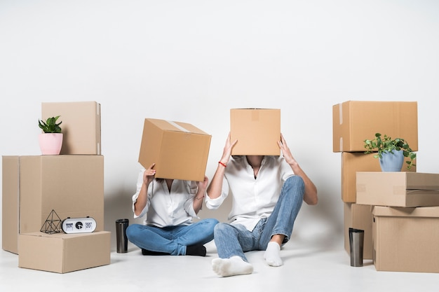 Young man and woman covering heads in boxes Premium Photo
