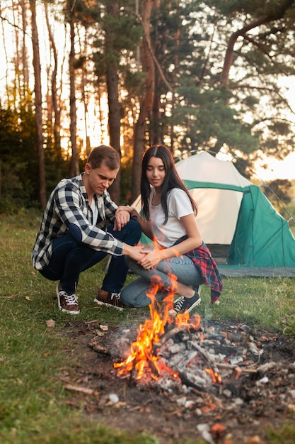 Young man and woman having a bonfire outdoors Free Photo