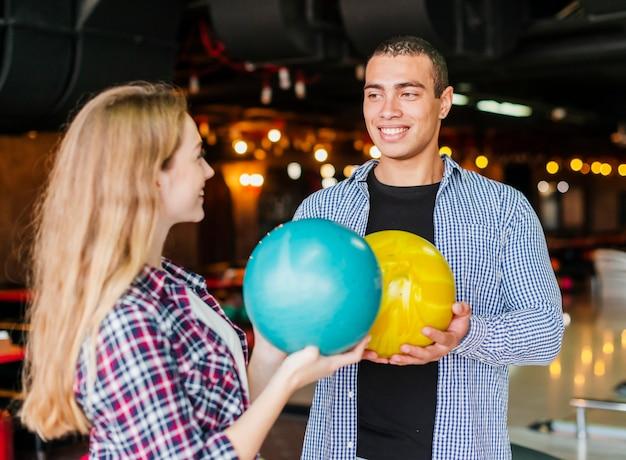 Giovane e donna divertirsi in un club di bowling Foto Gratuite