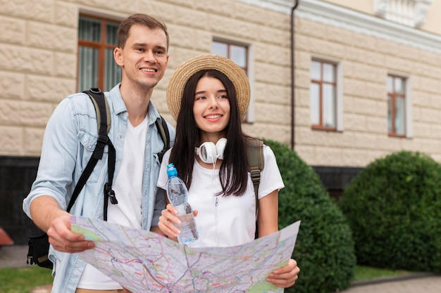 Young man and woman holding a map Premium Photo
