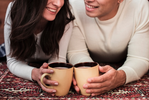 Young man and woman holding mugs Free Photo