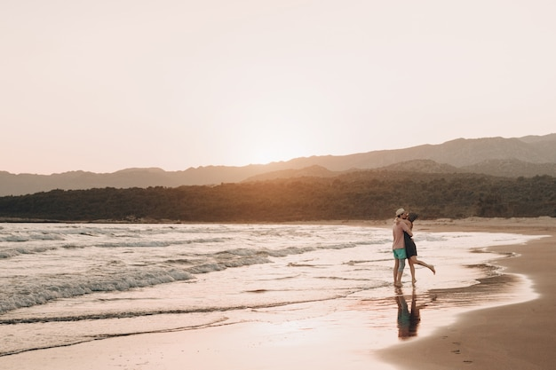 Young man and woman kissing on beach at sunset. Free Photo