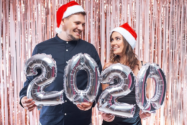Young man and woman in red santa hats having fun with 2020 metallic balloons. Premium Photo