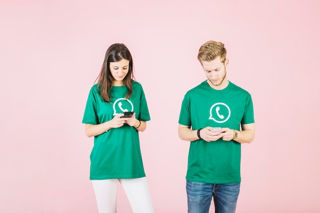 Young man and woman using mobile phone on pink background Free Photo