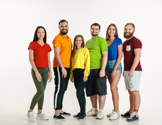 Young man and woman weared in lgbt flag colors on white wall. caucasian models in bright shirts. look happy, smiling and hugging. lgbt pride, human rights and choice concept. Free Photo
