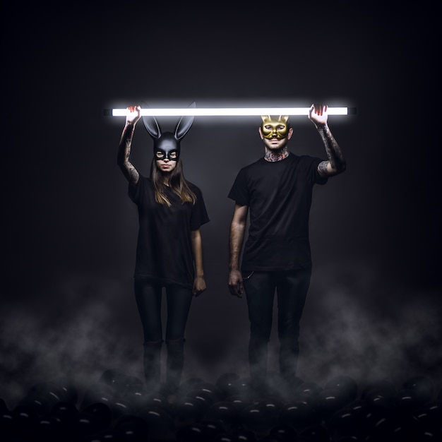 Young man and woman wearing black clothes and masks of a rabbit and cat with a light over them Free Photo