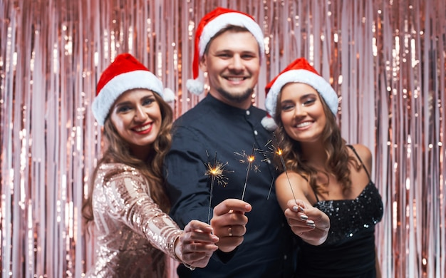 Young man and women enjoying christmas with sparklers in hands. Premium Photo