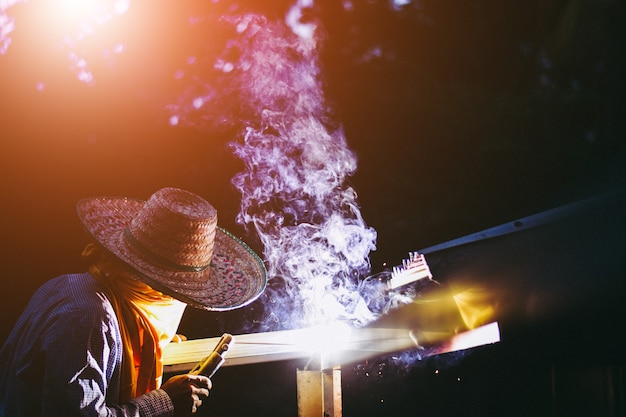 Young man worker welding iron pieces at work with protective goggles Premium Photo