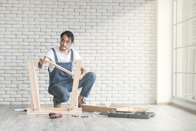 Young man working as handyman, assembling wood table with equipments Premium Photo