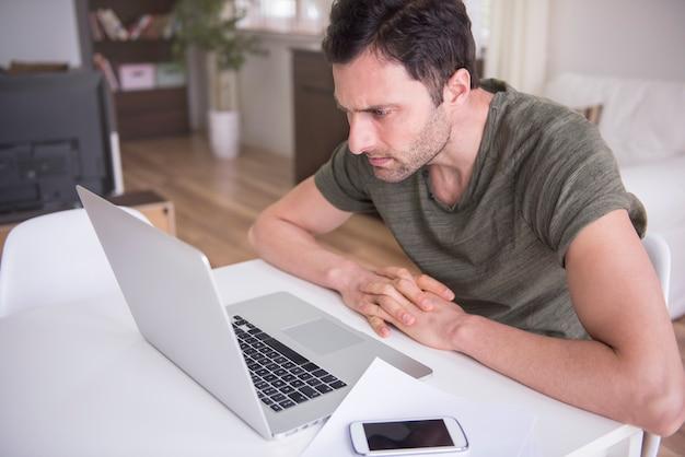 彼のラップトップで自宅で働く若い男 無料写真