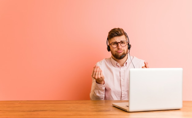 Young man working in a call center showing that he has no money. Premium Photo