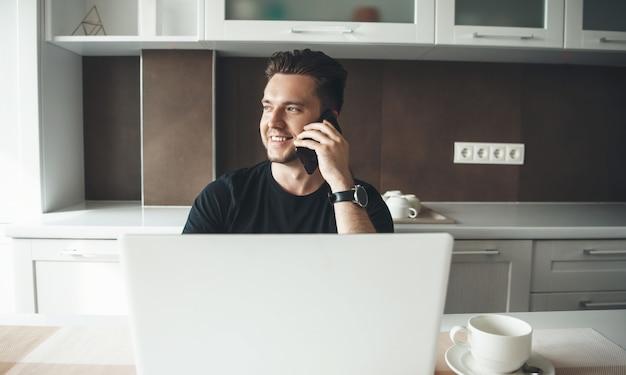 モバイルと笑顔で話しているラップトップで自宅のキッチンで働く若い男 Premium写真