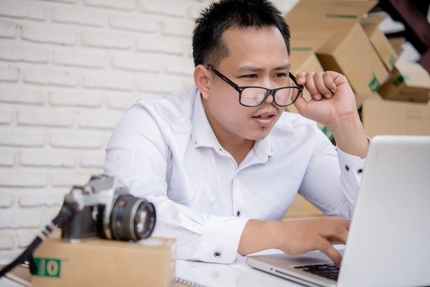 Young man working marketing online with laptop and box post Free Photo