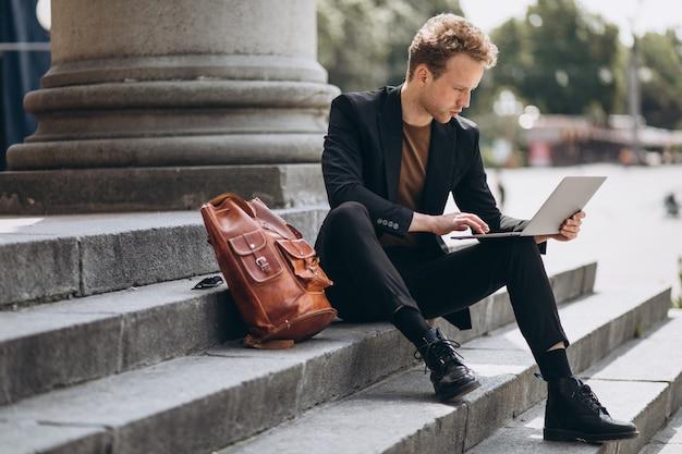 若い男が大学でコンピューターに取り組んで 無料写真