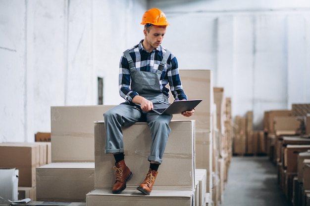 Young man working at a warehouse with boxes Free Photo