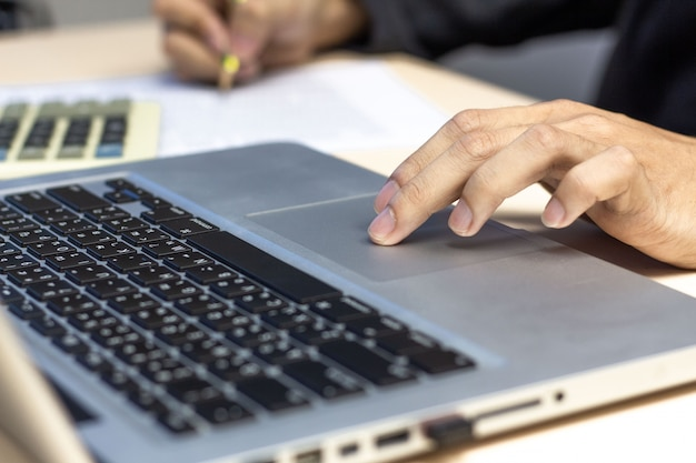Young man working with laptop, hand on touchpad of laptop. Premium Photo