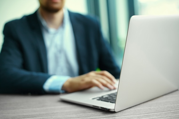 Young man working with laptop, man's hands on notebook computer, business person at workplace Free Photo