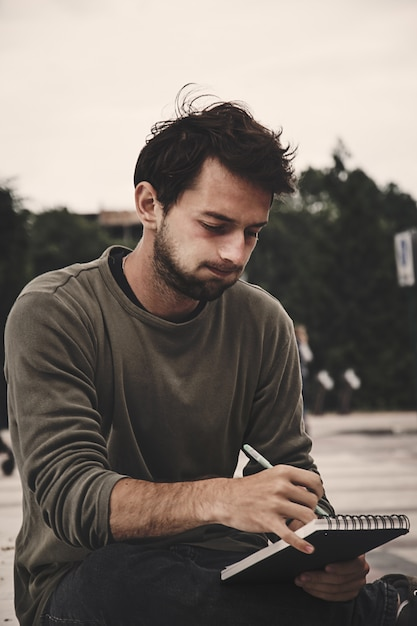 Young Man Writing In Notebook At Nature Side View Profile Of Bearded Man Drawing Premium Photo