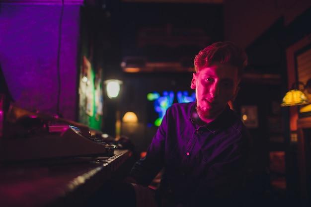 若い男が古いタイプライターで書きます。暗い照明、レストラン、モダンな服、古い作家の習慣 Premium写真