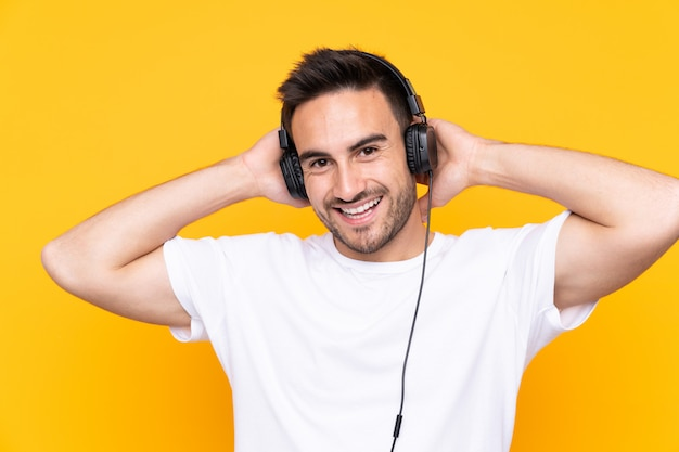 Young man over yellow listening music Premium Photo
