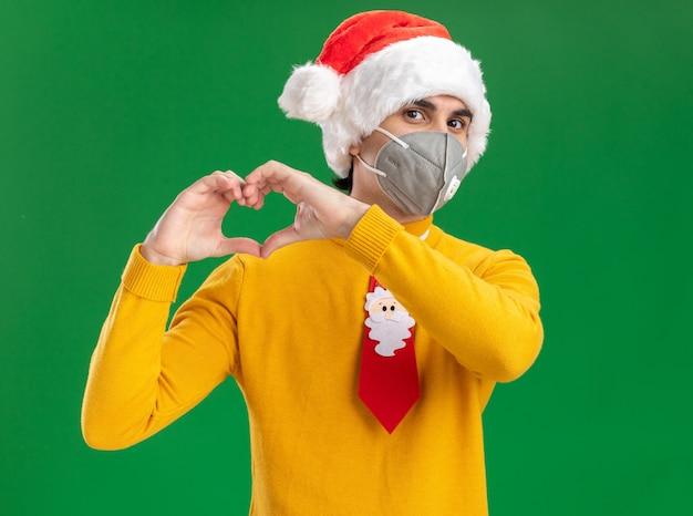 Giovane uomo in dolcevita giallo e cappello da babbo natale con cravatta divertente che indossa la maschera protettiva per il viso che fa il gesto del cuore con le dita in piedi su sfondo verde Foto Gratuite