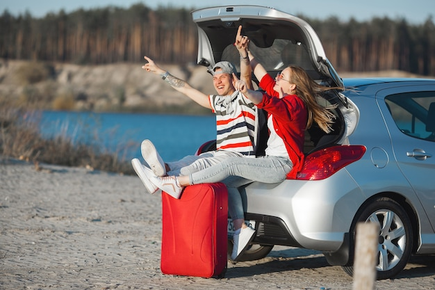 Young married couple in vacation. journey on the car. car trip. emotional young people traveling. Premium Photo