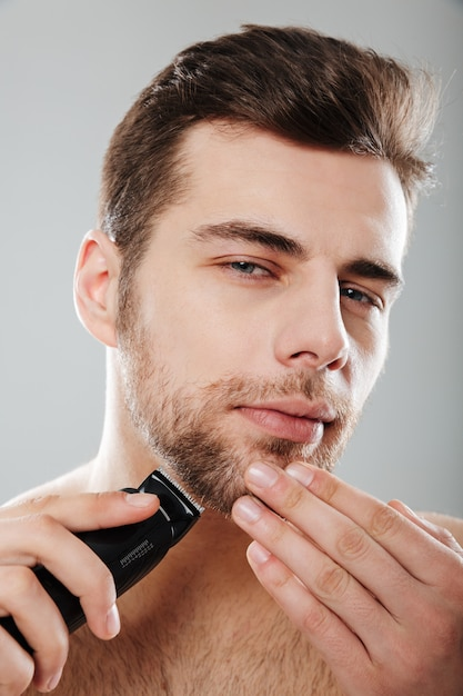 Young masculine male looking at camera being undressed and isolated at home having skincare while shaving his face with trimmer against grey wall Free Photo