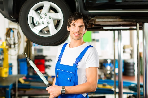 Young mechanic in blue overall working on car Premium Photo