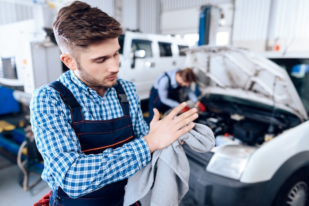 Young mechanic wipes hands with towel in garage. Premium Photo