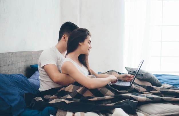 若い男性と女性はコンピューターで作業しているか、ベッドの上のインターネットで情報を探しています。 Premium写真