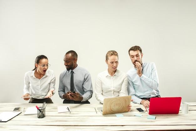 Молодые мужчины и женщины сидят в офисе и работают на ноутбуках. концепция эмоций Бесплатные Фотографии